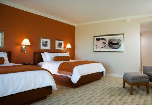 Large hotel room with two queen beds with white linens