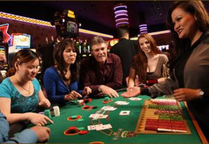One man and three women looking at the dealer's card in poker