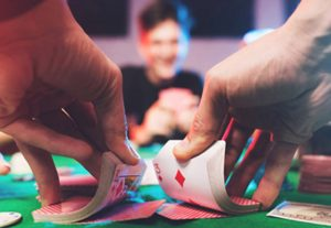 Dealer shuffling poker deck in front of man