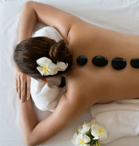 Women laying down at spa with hot stones down her back